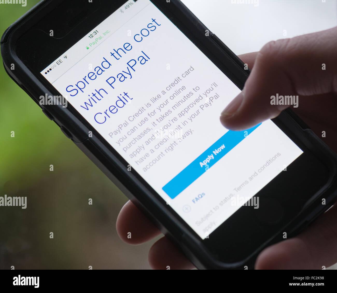 Young man holding smart phone à la recherche à la demande de crédit PayPal Photo Stock