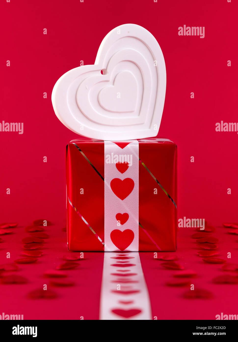 Blanc forme coeur plus de boîte-cadeau sur fond rouge. La Saint-Valentin et l'amour gratuit. Photo Stock