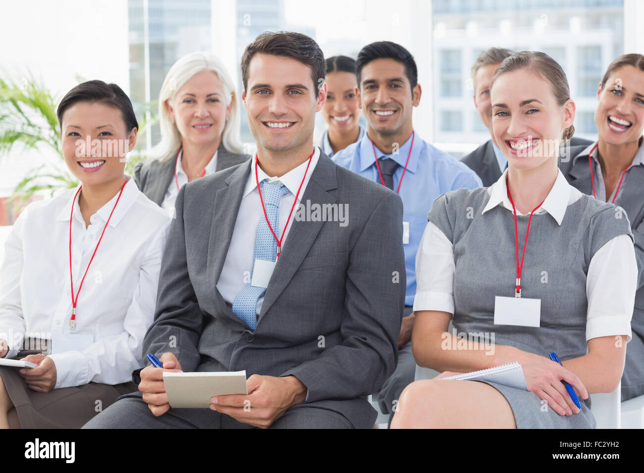 Smiling business people looking at camera during meeting Photo Stock