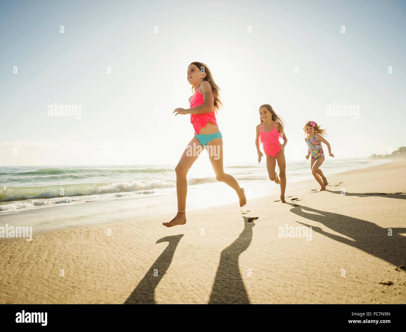 Sœurs de race blanche running on beach Banque D'Images