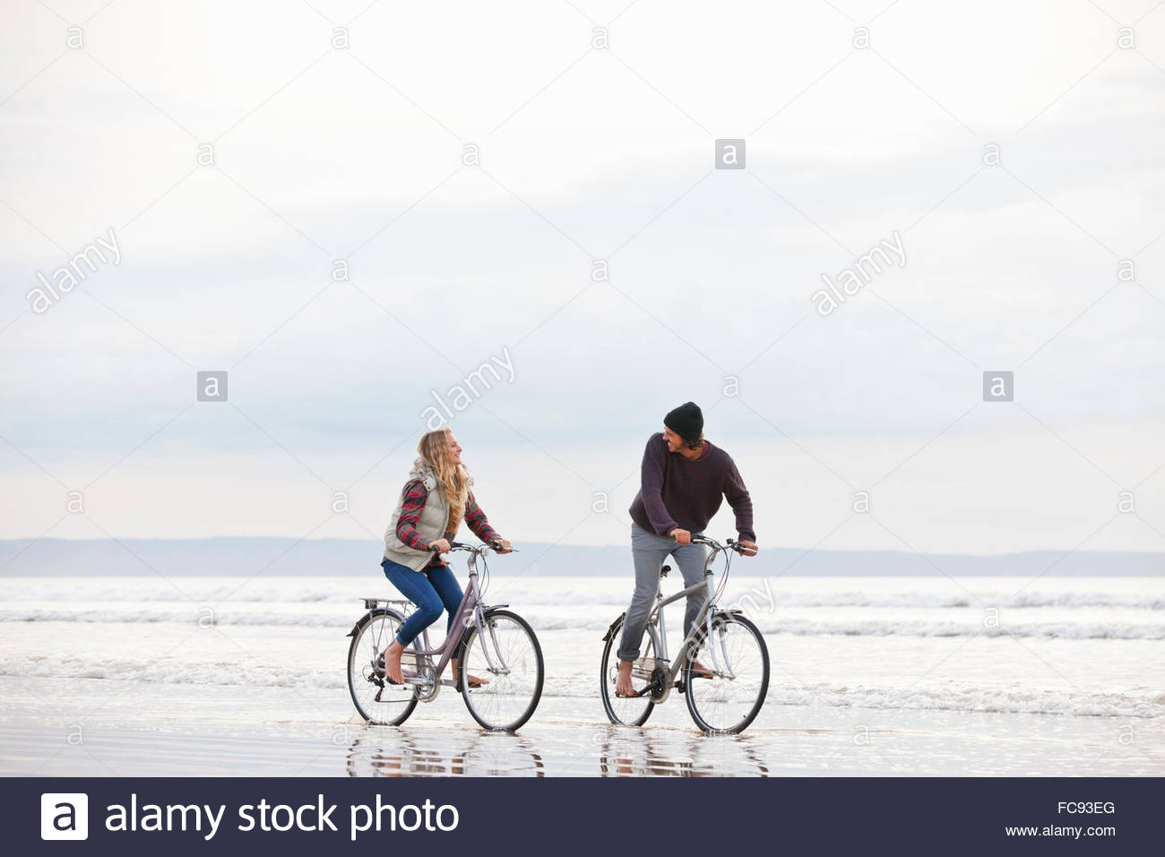 Couple riding bicycles dans océan surf Photo Stock