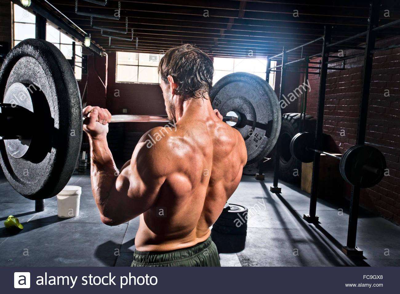 Un athlète crossfit effectue des biceps. Photo Stock