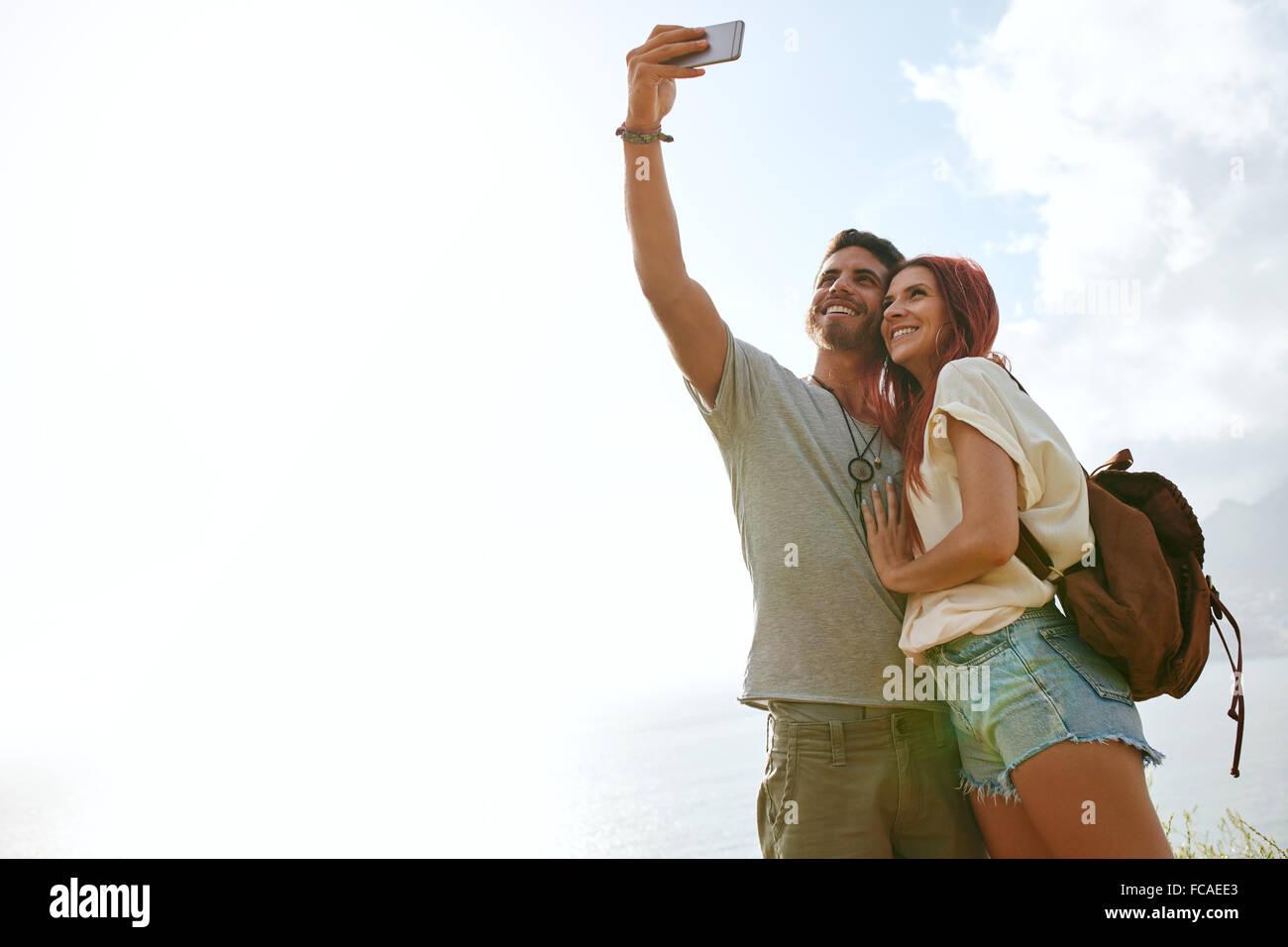 Low angle view of loving couple jeune en vacances en prenant un autoportrait avec le smartphone à l'extérieur. Photo Stock