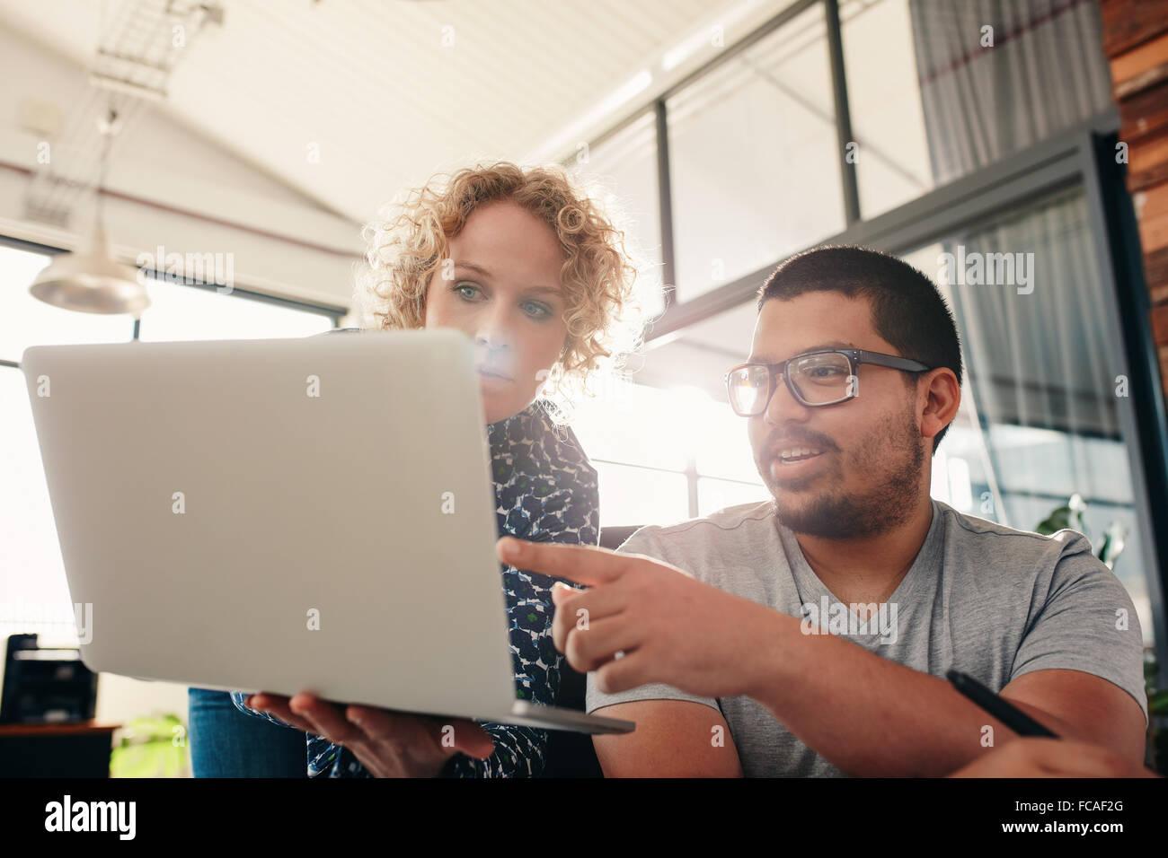 Deux jeunes graphistes travaillent dans leur propre bureau. Man pointing at laptop in women's hands. Photo Stock