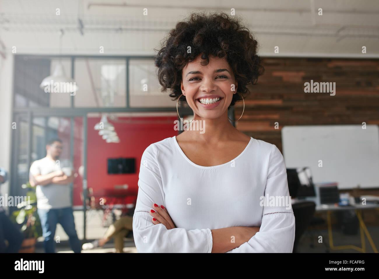 Jeune femme debout avec les bras croisés et regarder la caméra. Elle est debout dans un bureau moderne avec ses collègues Banque D'Images