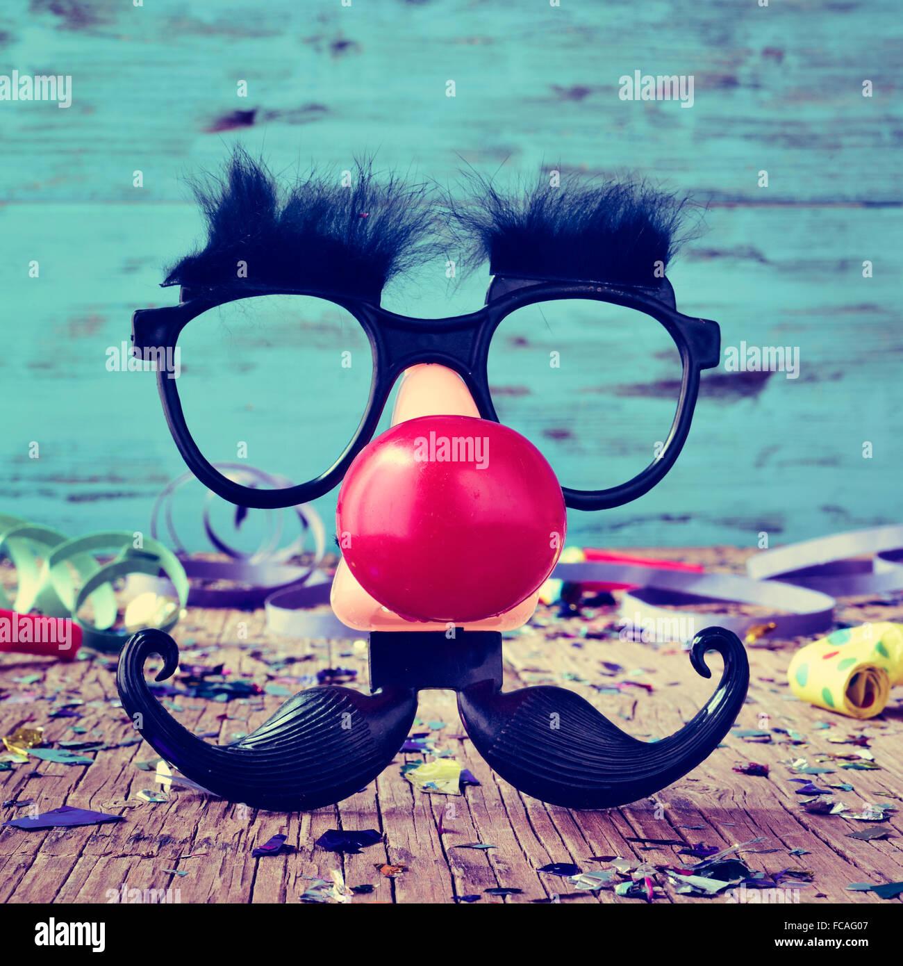 Une paire de lunettes noires avec de faux sourcils, un nez de clown rouge et 9bf55179ae97