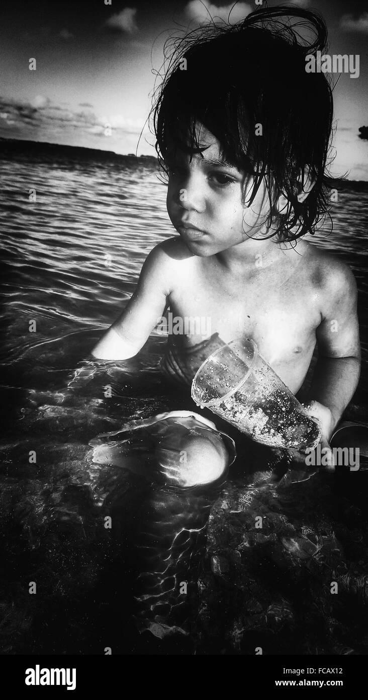 Cute Boy avec conteneur en verre assis sur mer Photo Stock