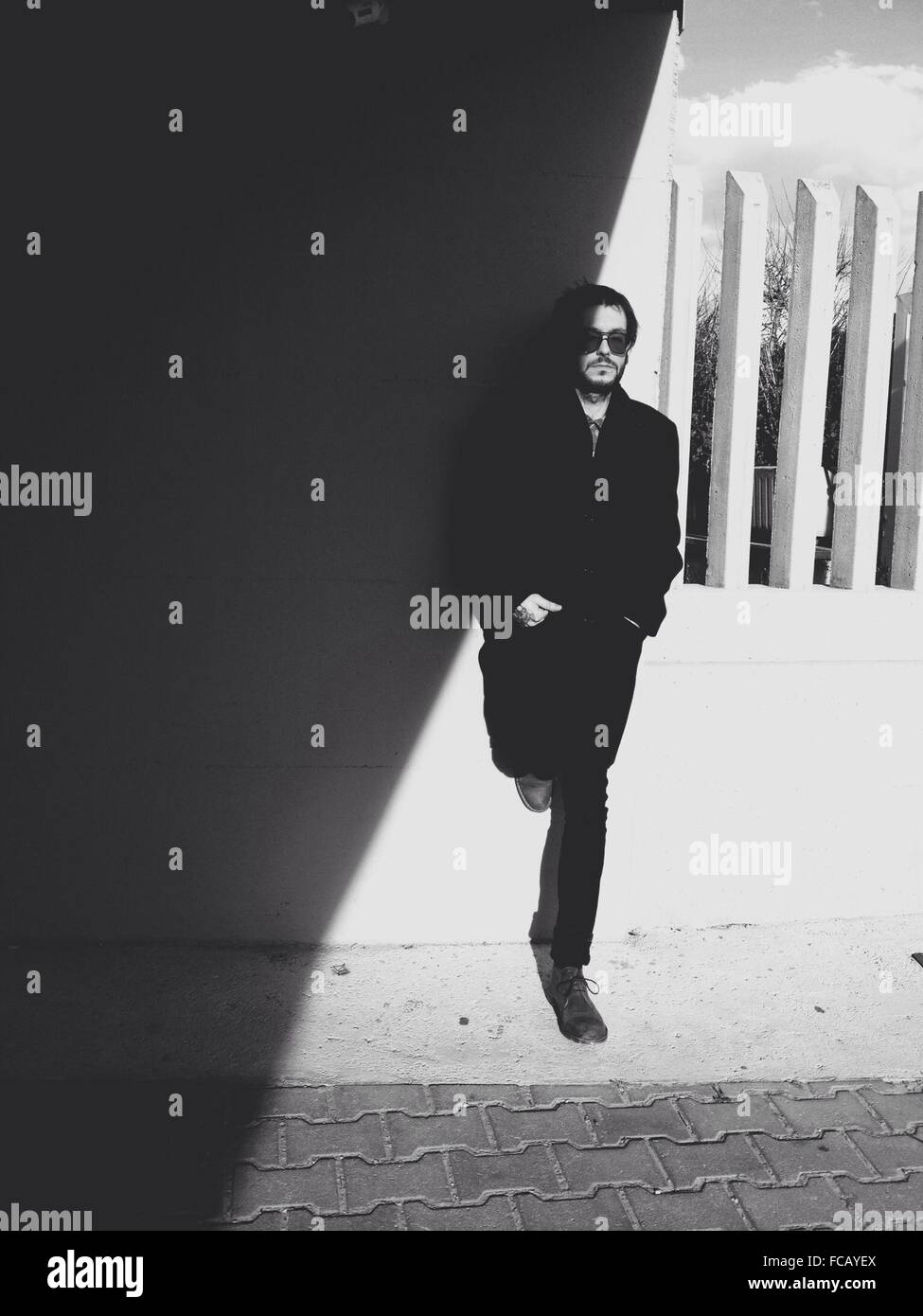 Toute la longueur de Young Man Leaning On Wall At Sidewalk Photo Stock