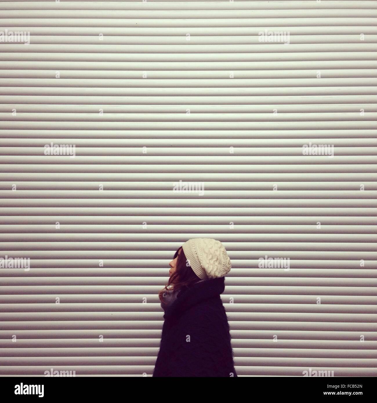 Vue de côté Femme Debout contre l'atelier fermé Photo Stock