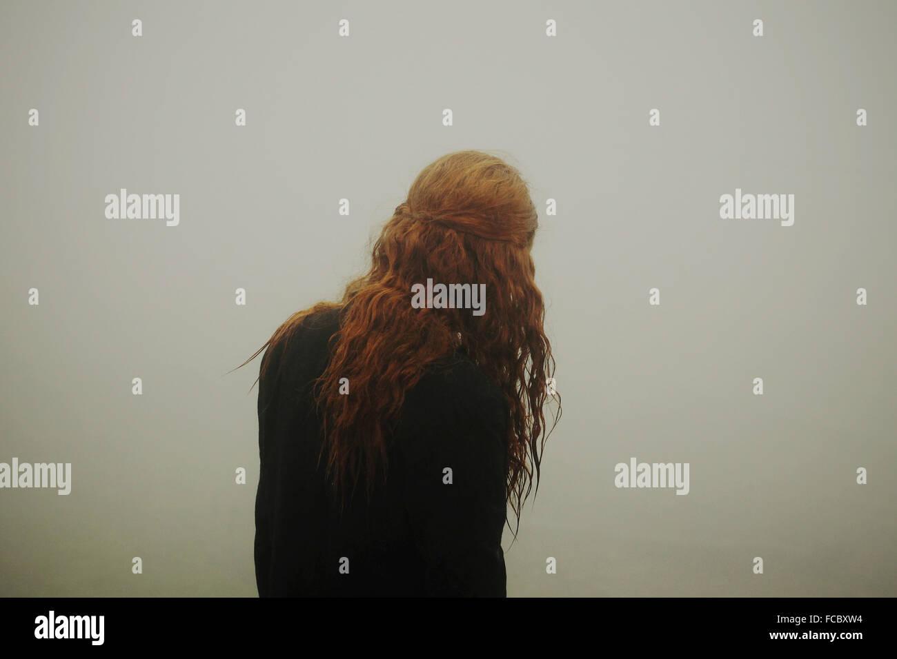 Vue arrière d'une femme aux longs cheveux rouges Photo Stock