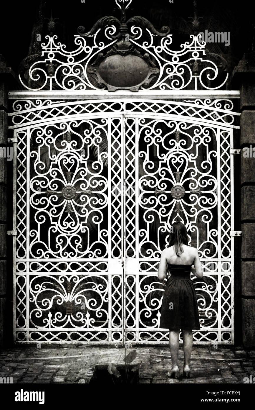 Vue arrière de la femme debout devant de grandes portes fermées Photo Stock