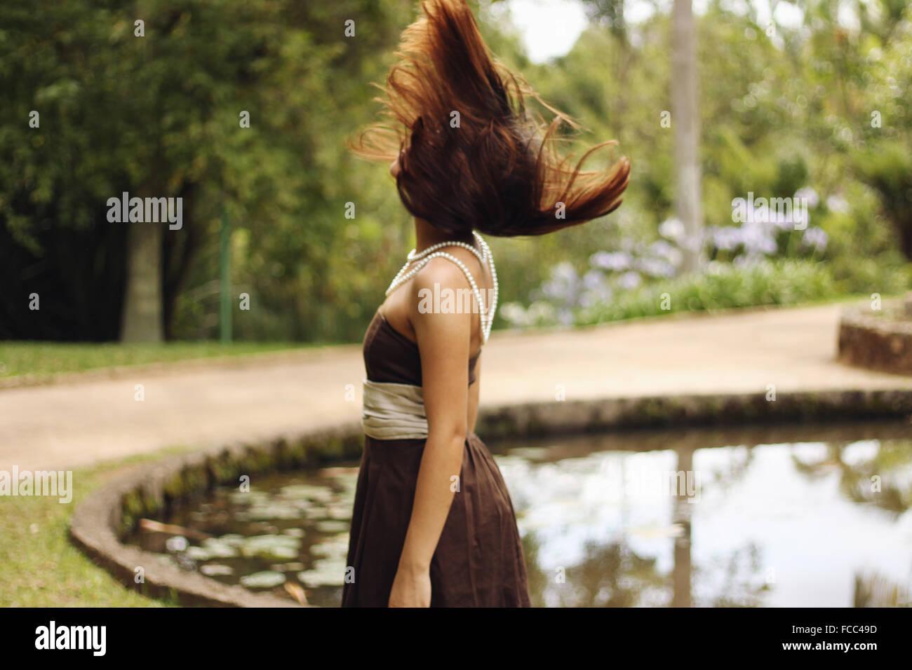 Vue latérale d'une femme avec les cheveux bruns soufflé par Campagne Lac Photo Stock