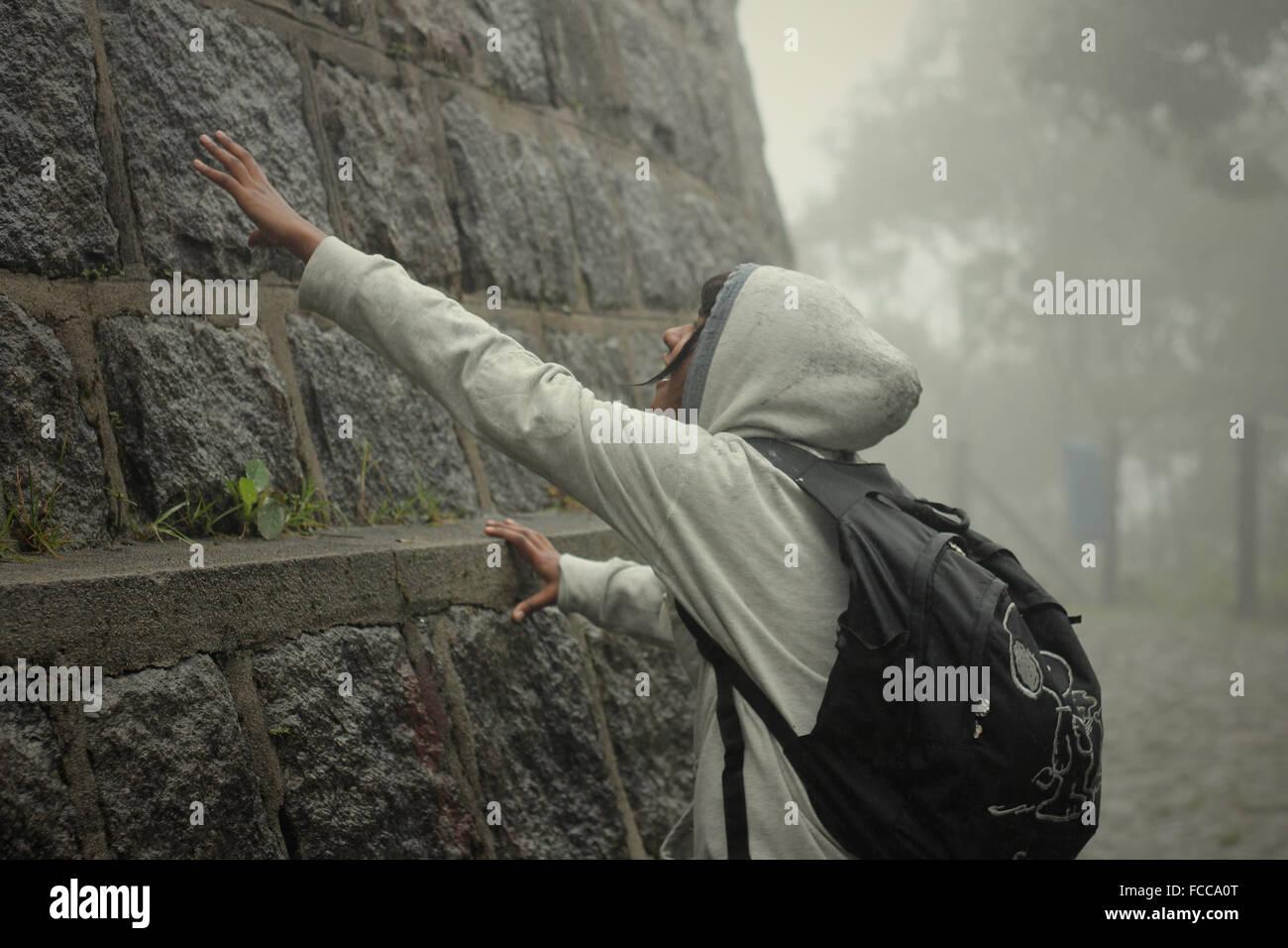Adolescent touchant mur de pierre Photo Stock