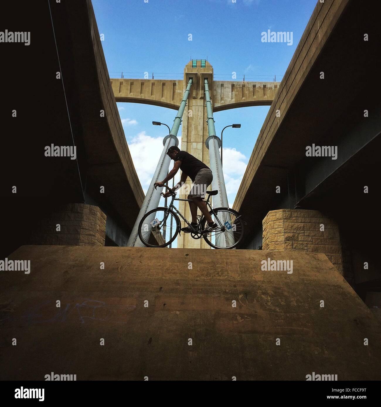 Low Angle View Of Man en équilibre sur vélo le long Bridge Banque D'Images