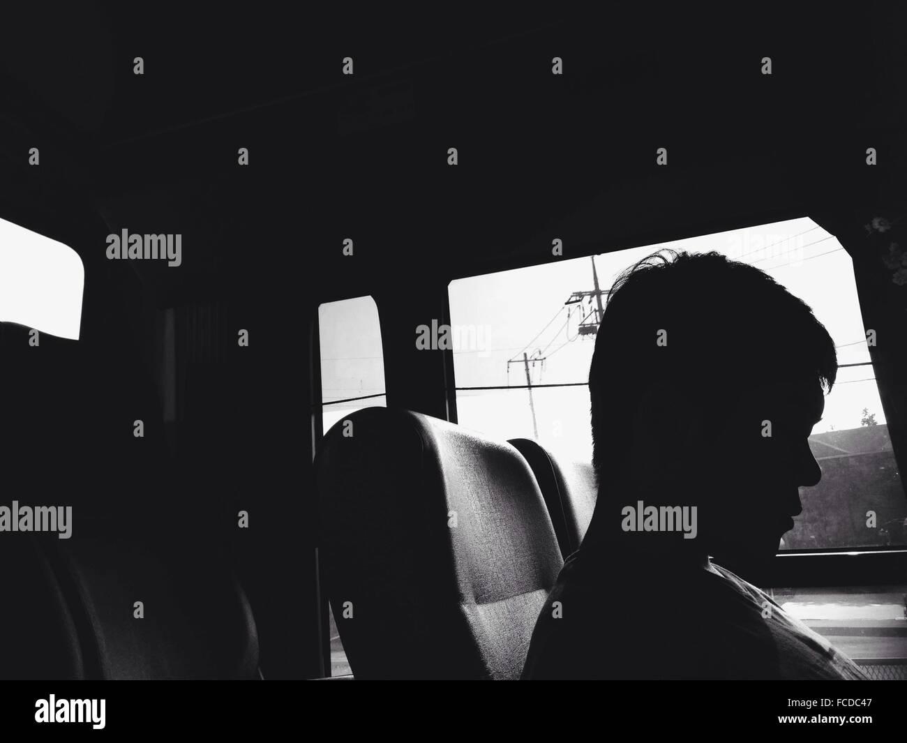 Silhouette de l'homme assis à l'intérieur de voiture Photo Stock