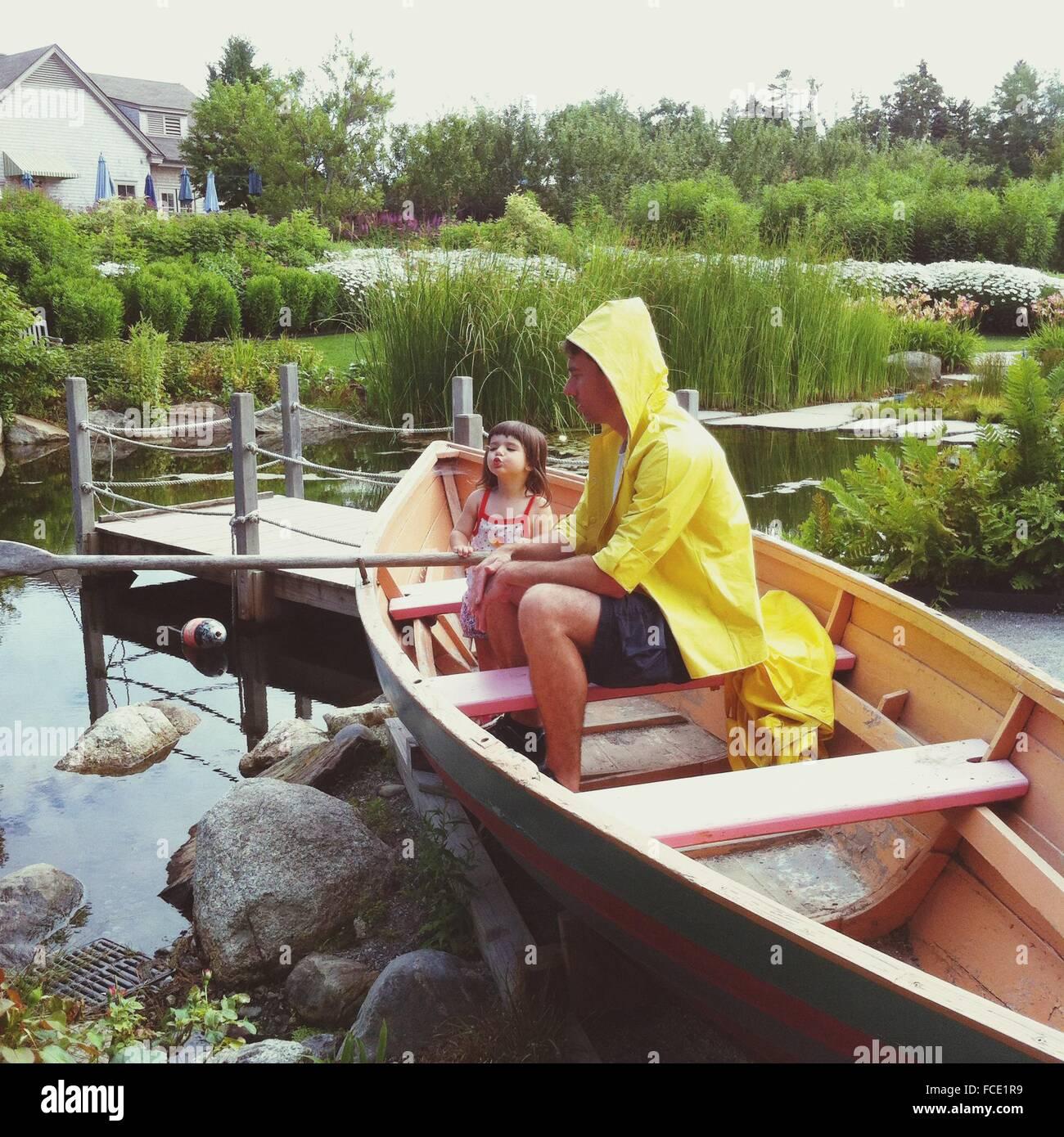 Homme assis dans un bateau avec sa fille Photo Stock