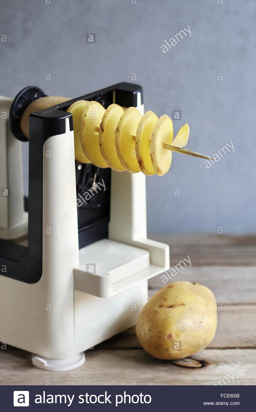 Spirale de pommes de terre avec un spiralizer machine Photo Stock