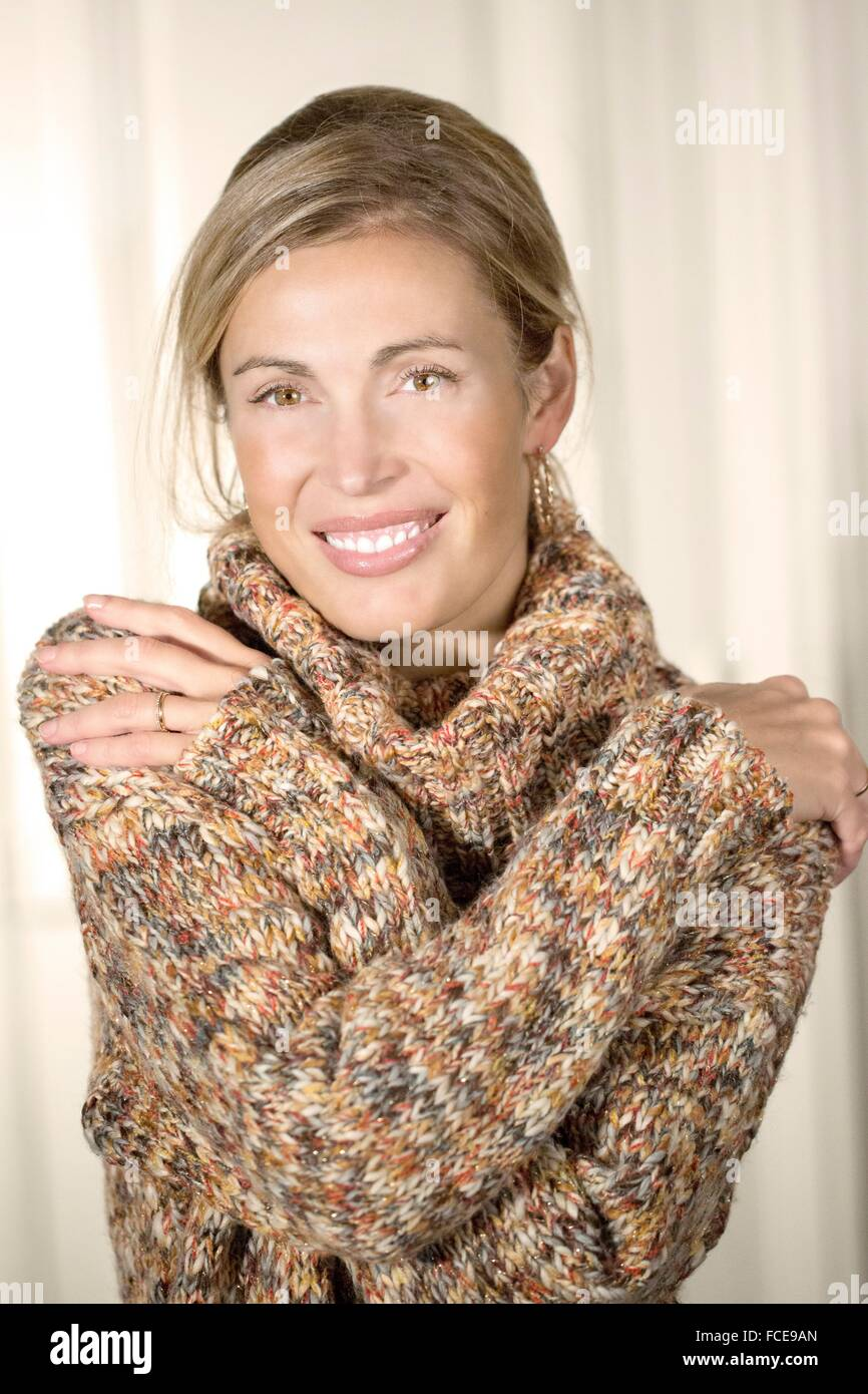 Close-up of young woman smiling with sweater Photo Stock