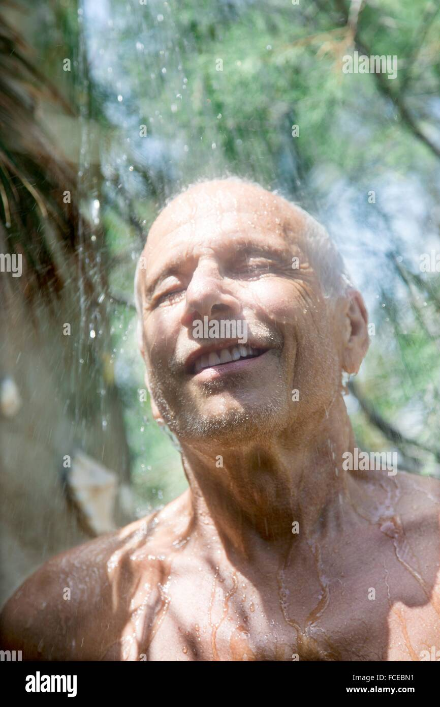 Close-up of smiling man prendre une douche à l'intérieur Photo Stock
