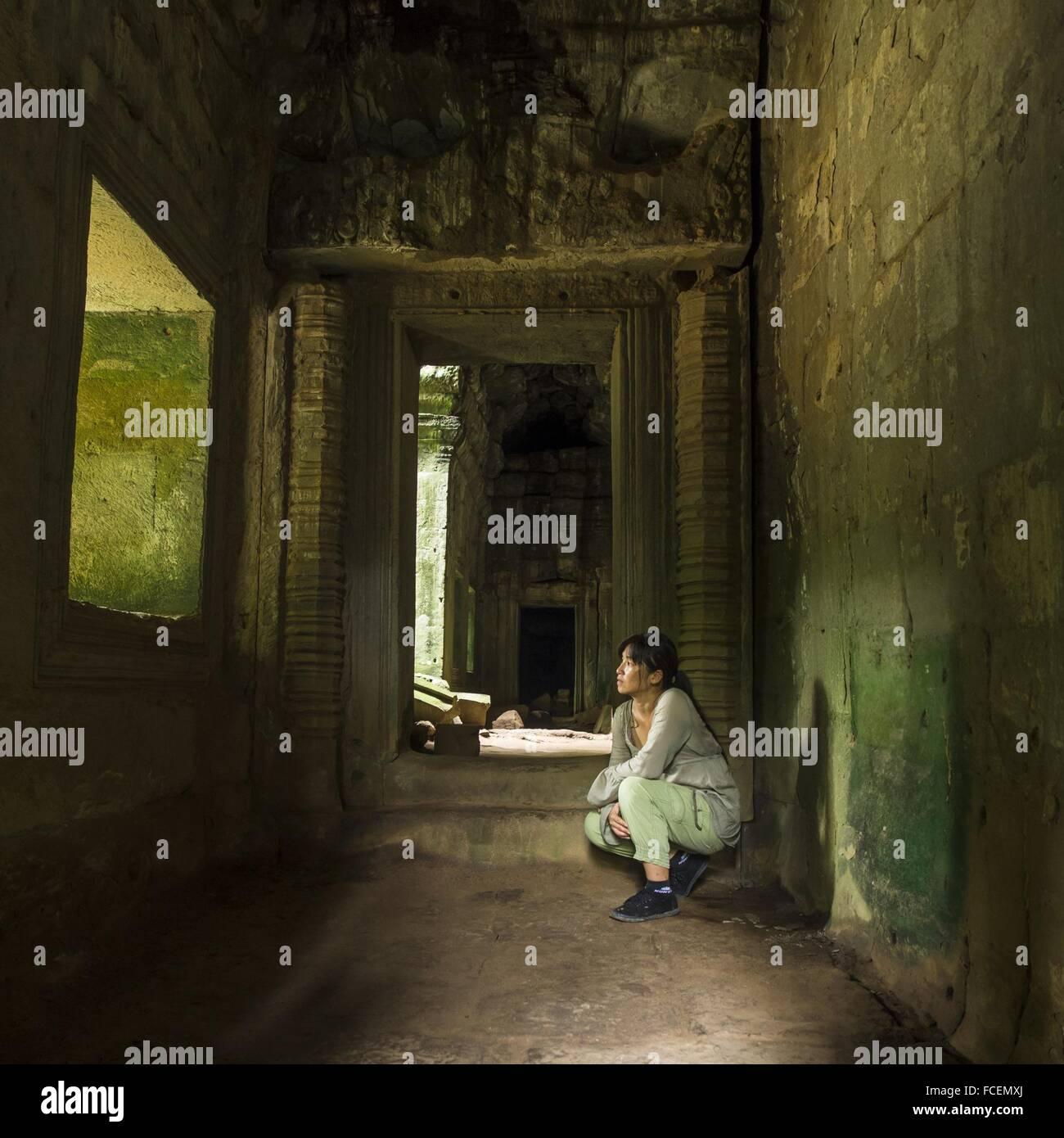 Toute la longueur de femme accroupie dans la maison abandonnée Photo Stock