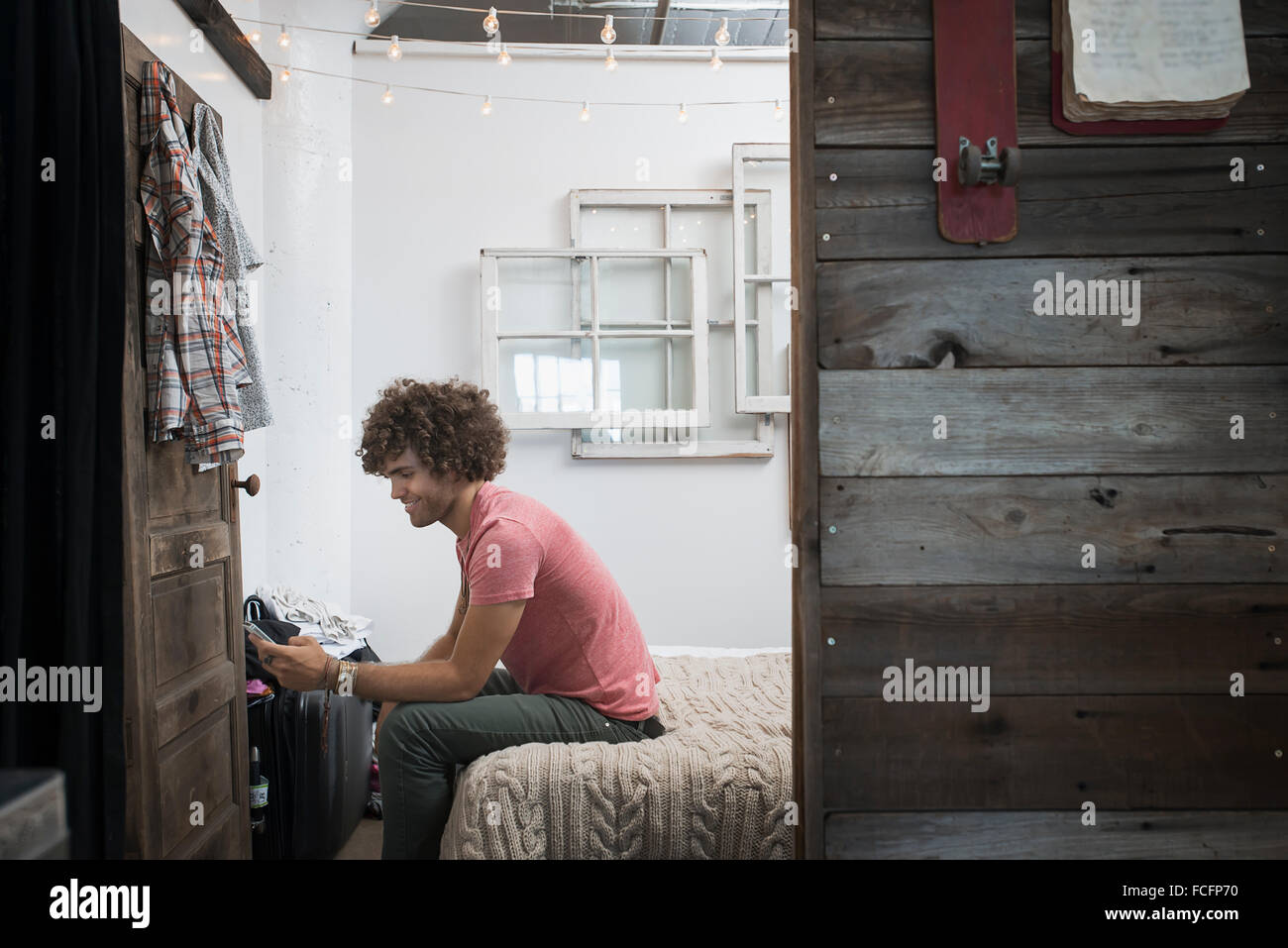 Loft vivant. Un jeune homme à l'aide d'un téléphone intelligent. Photo Stock