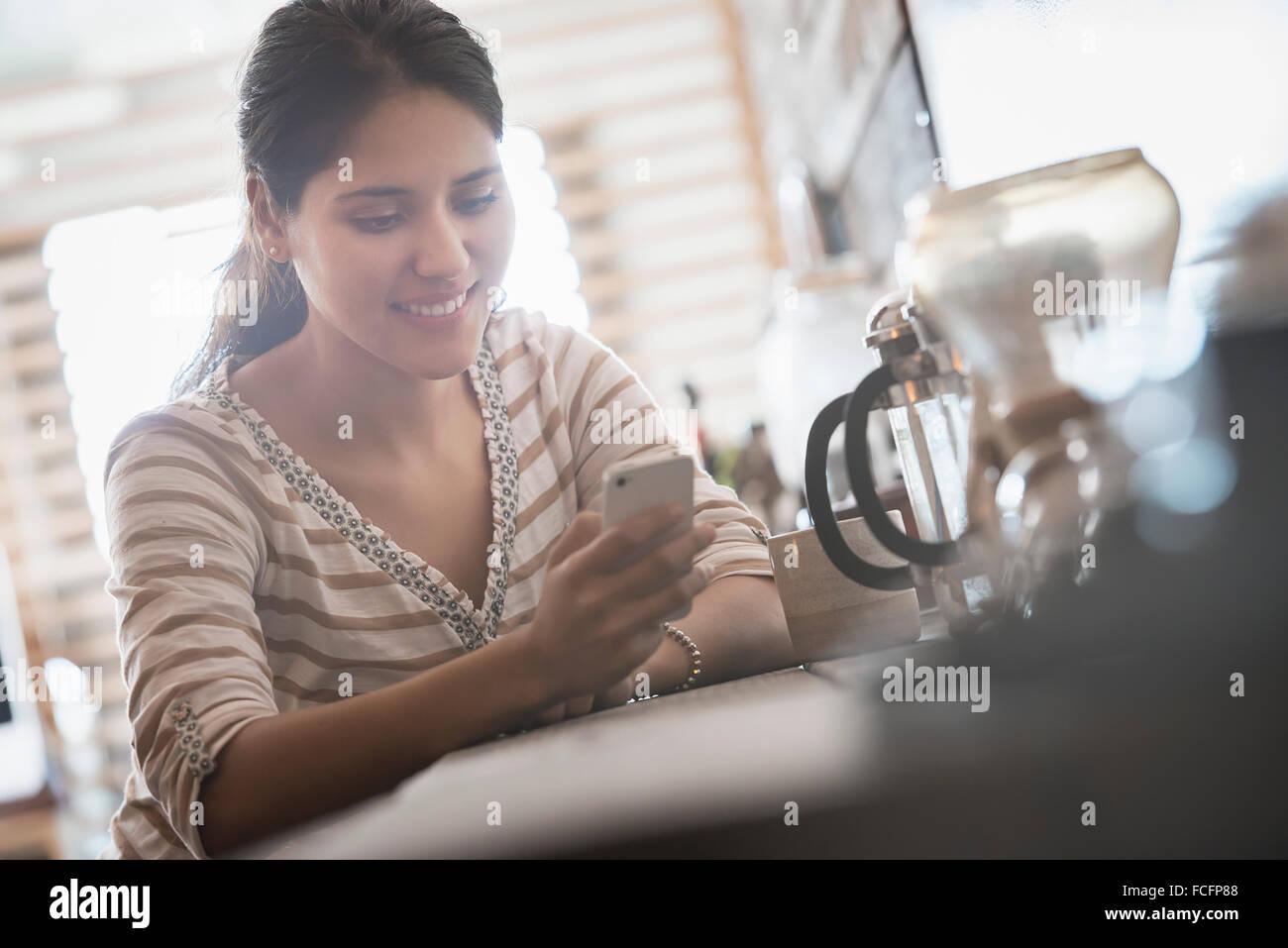 Loft vivant. Une femme à la recherche de son téléphone intelligent. Photo Stock