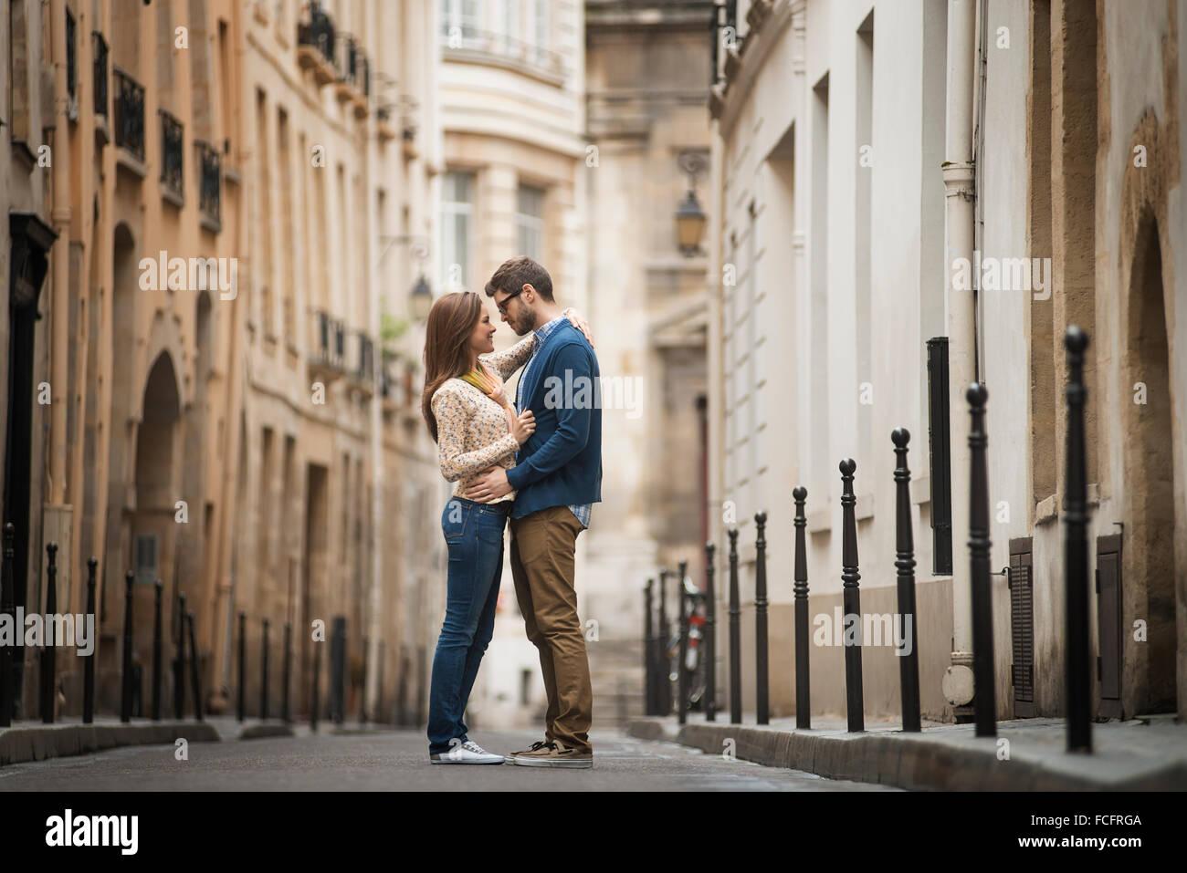 Un couple debout à regarder les uns les autres, dans une rue étroite dans une ville. Photo Stock