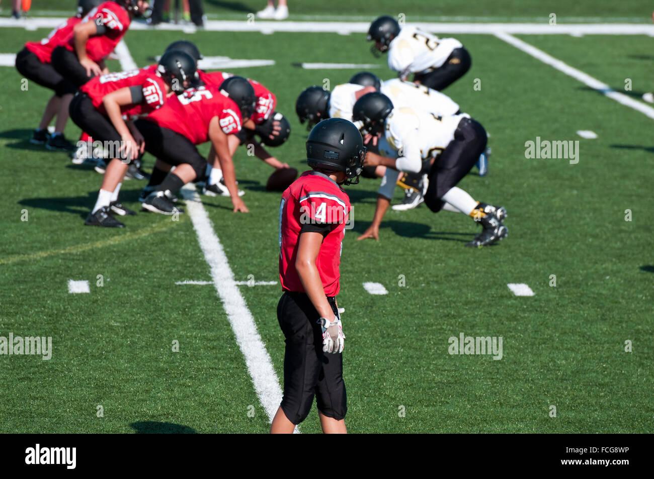 High School football américain receveur en attente de lecture pour commencer pendant le jeu. Photo Stock
