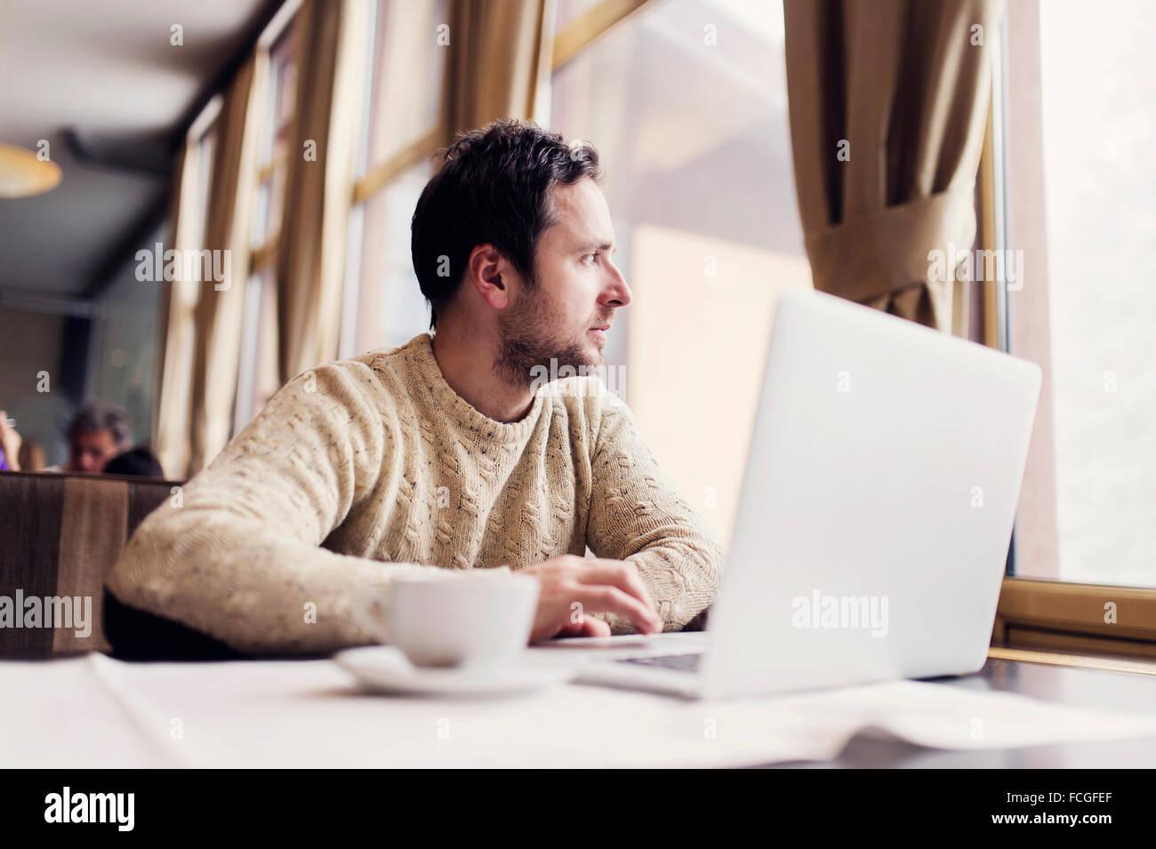 Ordinateur portable homme assis dans un café à la recherche d'une fenêtre Photo Stock