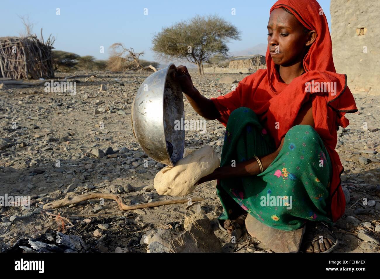 Femme de la tribu Afar la cuisson du pain avec une pierre chaude, Malab-Dei village, dépression Danakil, région Photo Stock