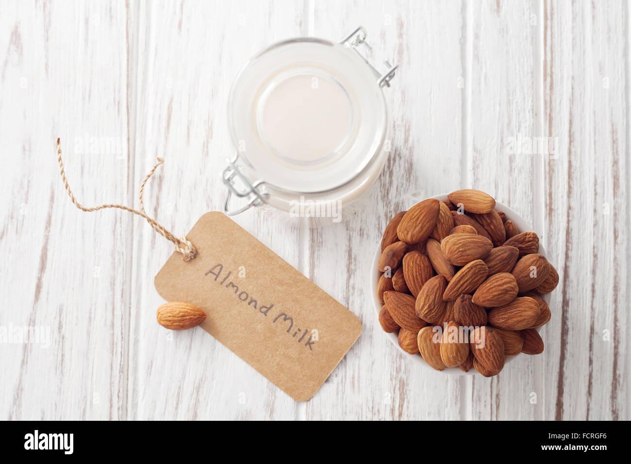 Bio au lait d'amande noix sain végétarien végétalien verre fond blanc bois rustique en teck Photo Stock
