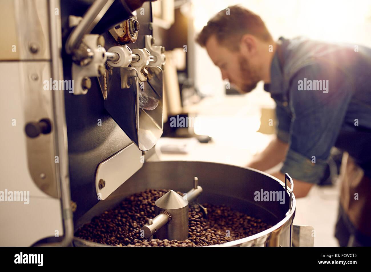 Les grains de café fraîchement torréfié dans une machine moderne Photo Stock