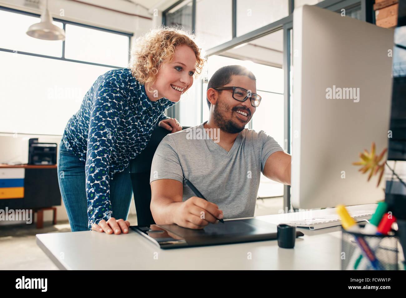 Deux jeunes designers, hommes et femmes travaillent ensemble, avec l'homme modification d'une illustration Photo Stock