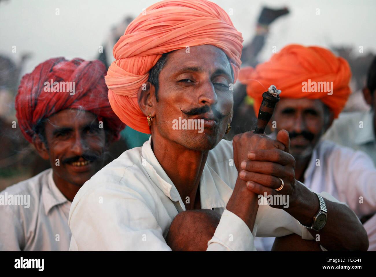 Râjasthânî chameliers fumeurs chillum, avec turban orange , à Pushkar, Rajasthan Banque D'Images