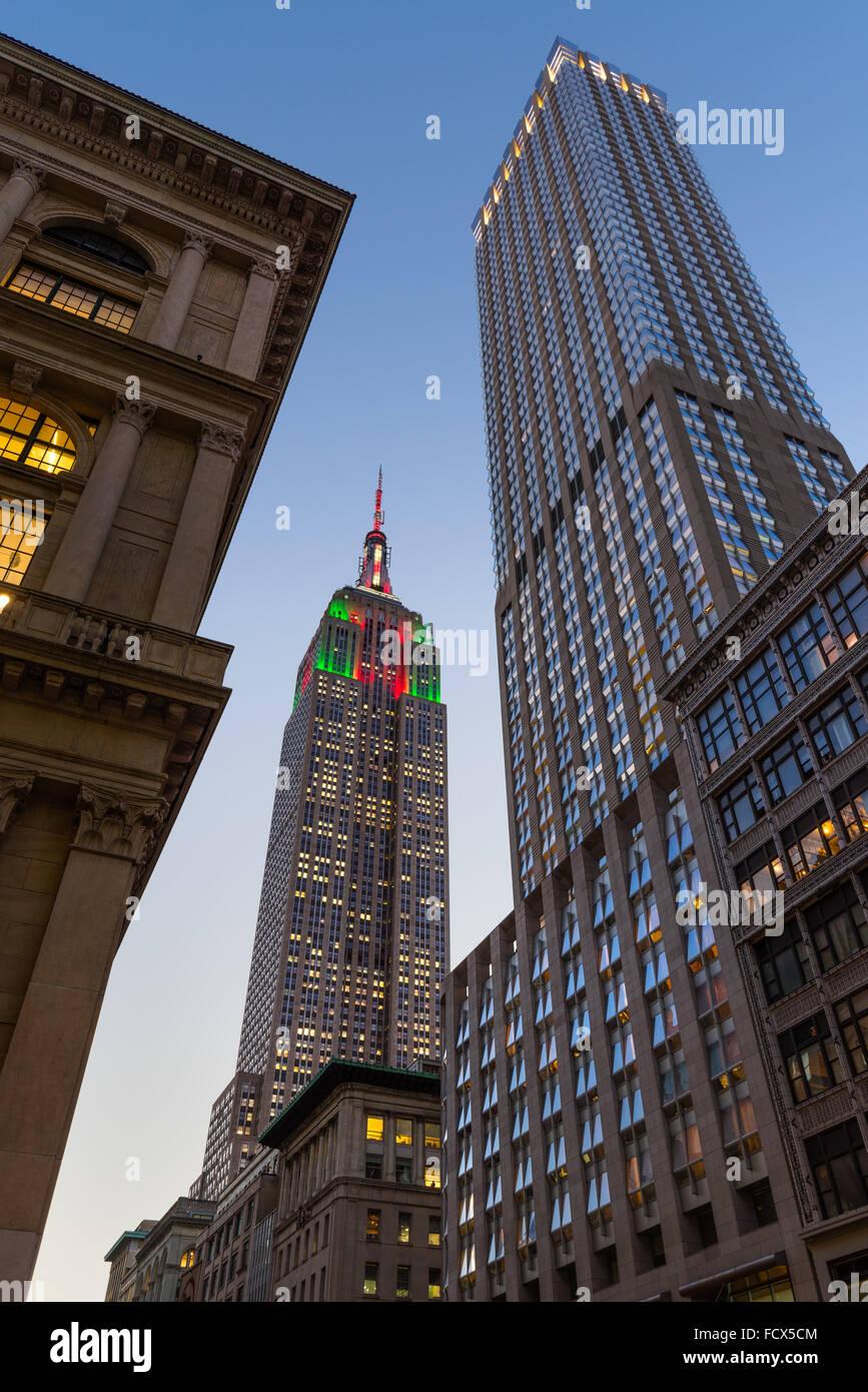 Au crépuscule de l'Empire State Building illuminé de rouge, vert et blanc des lumières de Noël. Photo Stock