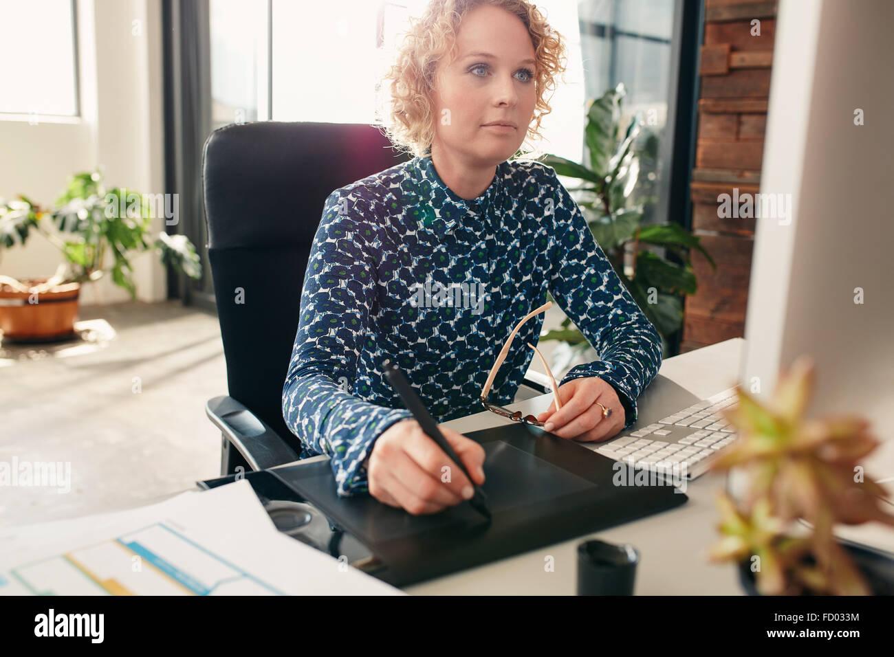 Jeune femme rédactrice à l'aide de tablette graphique pour travailler à son bureau dans le bureau. Photo Stock