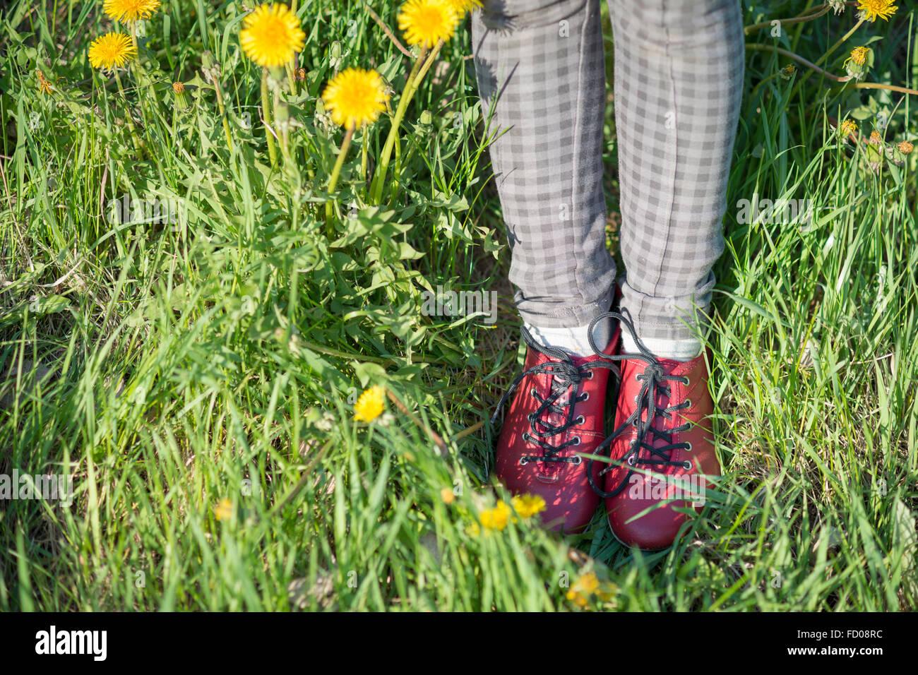 Jambes en chaussures rouges dans l'herbe verte avec des pissenlits en fleurs Banque D'Images