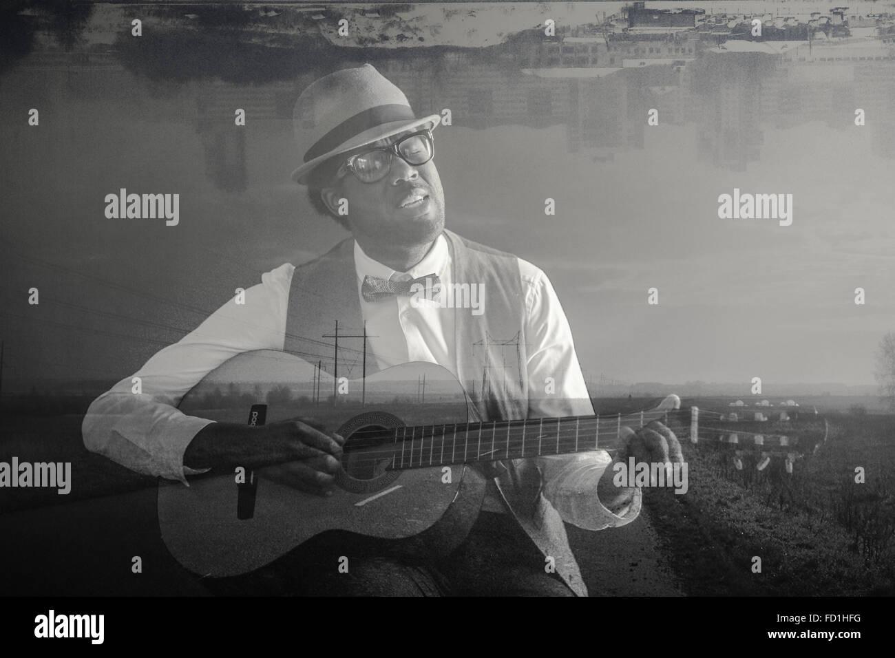 L'homme afro-américain qui joue de la guitare et chant, route rurale et à l'envers la réflexion Photo Stock
