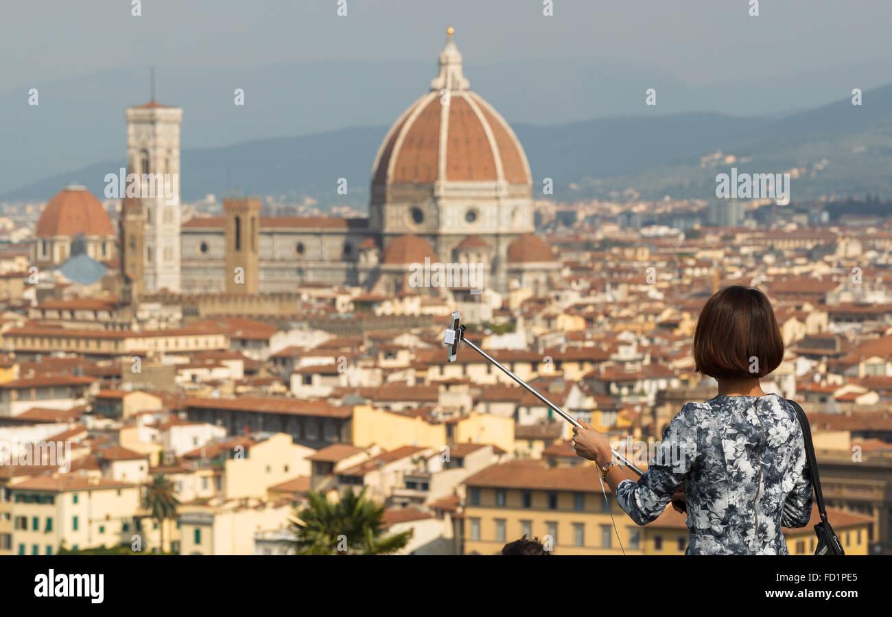 Une jeune femme se prépare à prendre un en selfies Piazzale Michelangelo, Florence, Toscane, Italie. Photo Stock