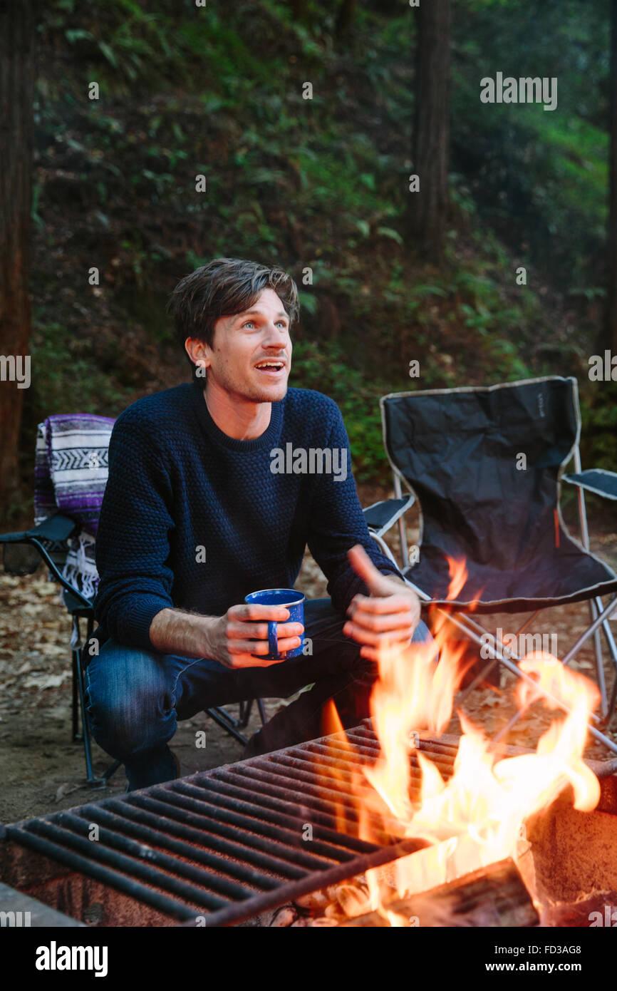 Un jeune homme est assis autour du feu en racontant des histoires avec des amis à Big Sur, en Californie. Photo Stock