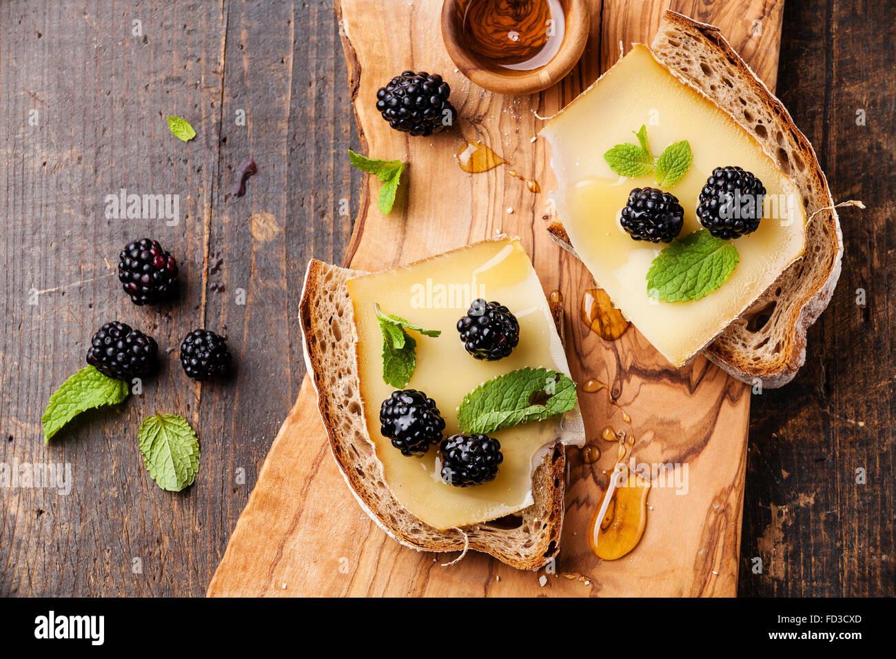 Sandwich avec du fromage et du pain frais sur blackberry sur fond de bois foncé Banque D'Images