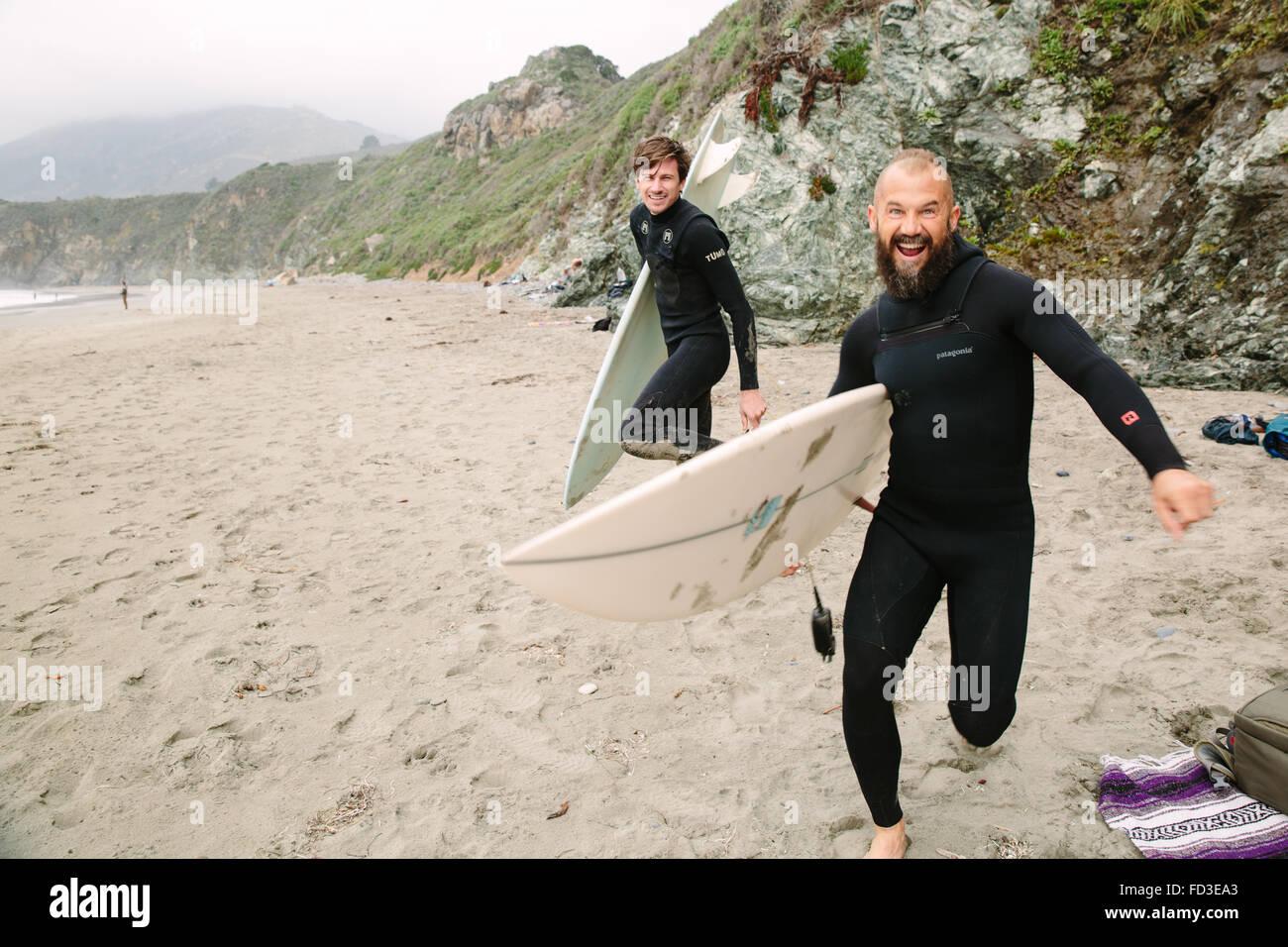 Deux surfeurs goof autour sur la plage avant de sauter dans l'eau pour attraper des vagues à Big Sur, en Californie. Banque D'Images