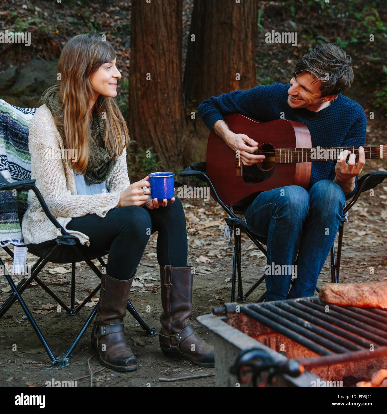 Un jeune couple est assis près du feu de camp profiter de la musique et la nature dans Big Sur, en Californie. Photo Stock