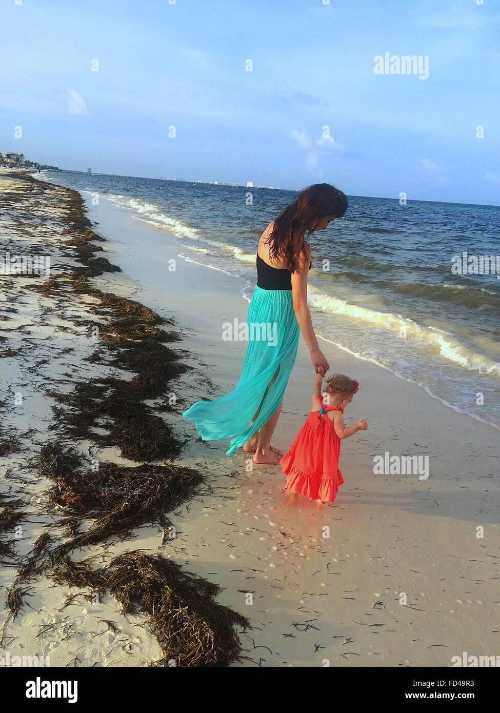 Femme avec son bébé sur la plage Photo Stock