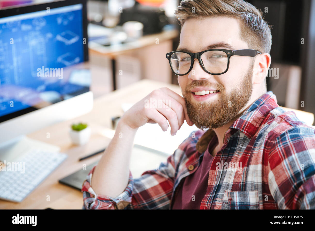 Happy young man with beard dans les verres et de la conception de projet sur son ordinateur Photo Stock