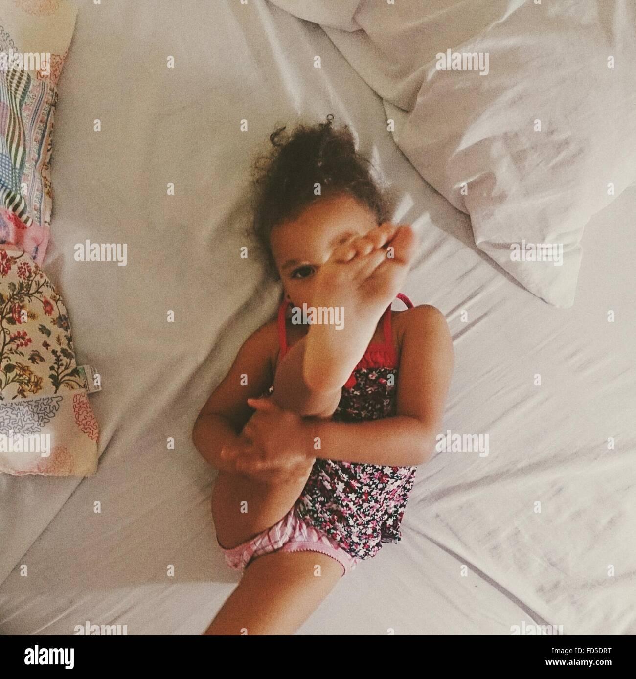 High Angle View of Girl avec pieds tout en vous relaxant sur le lit Photo Stock