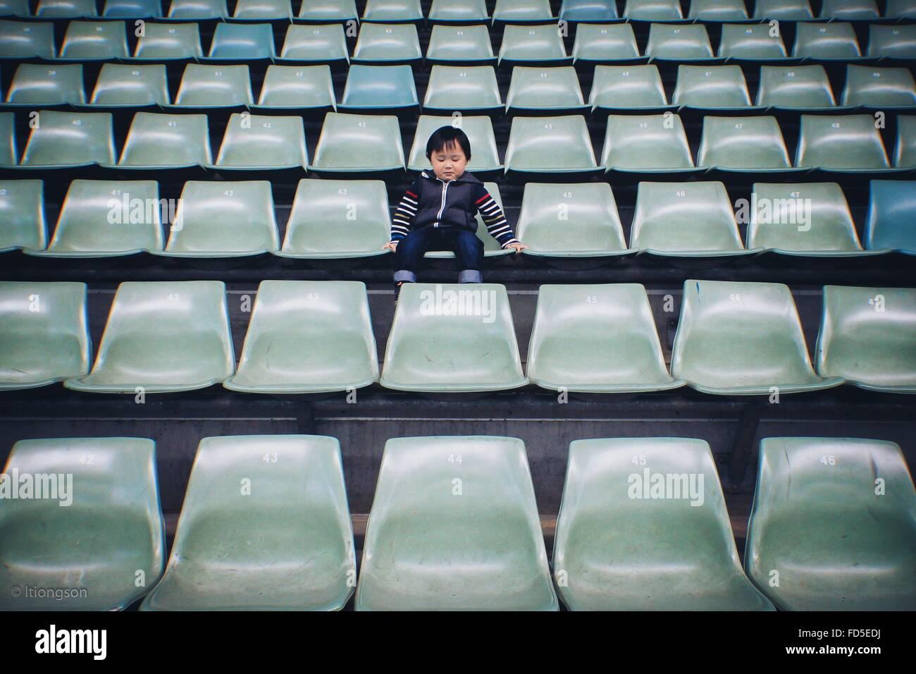 Garçon assis sur une chaise dans le stade Photo Stock