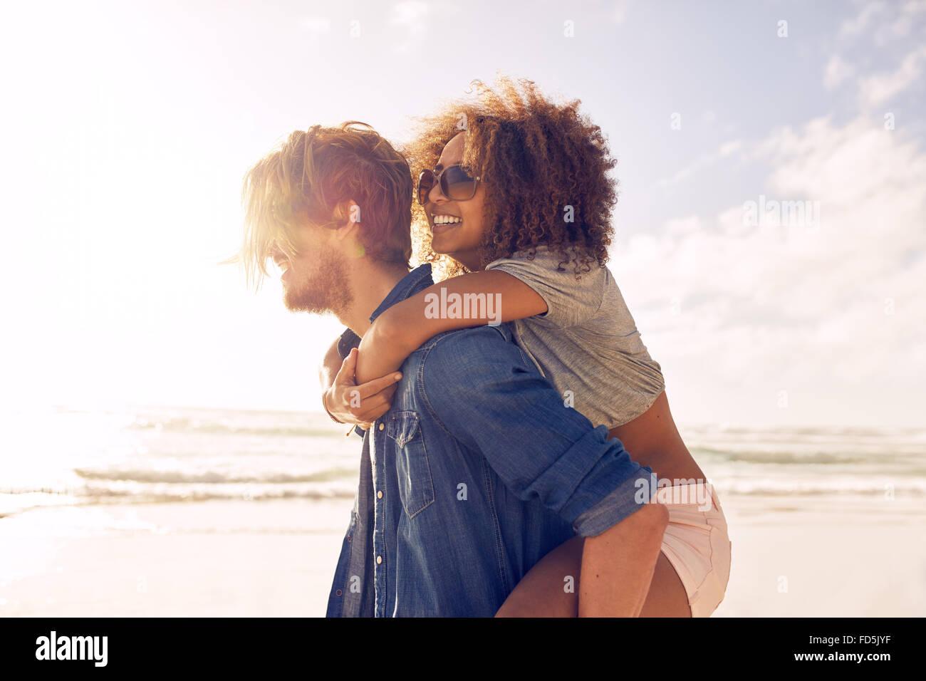 Vue de côté portrait of young man carrying son amie sur son dos à la plage. Donnant de petits amis piggyback ride Banque D'Images