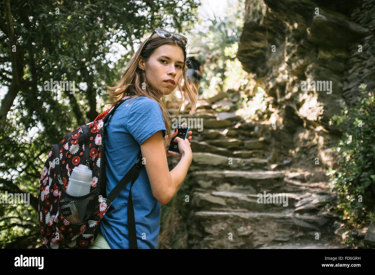 Jeune femme au pied de marches en pierre Photo Stock