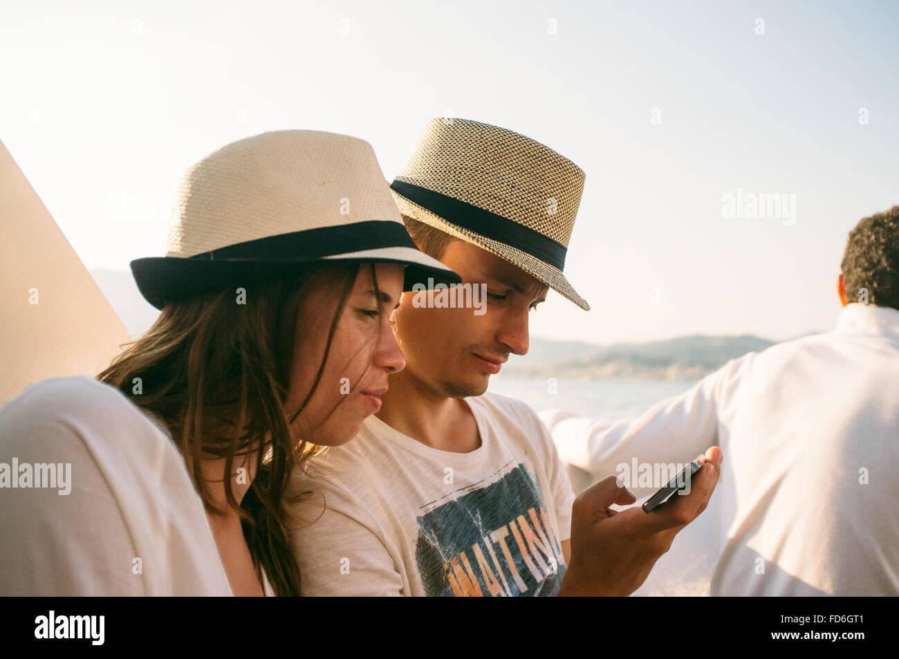 Jeune couple avec chapeau à l'aide de Smart Phone At Beach Photo Stock